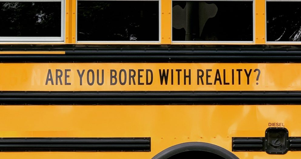 Are You Bored With Reality? written on side of a school bus